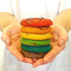 A chef holds a stack of colorful rainbow chocolate chip cookies.
